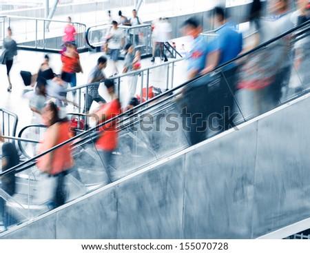 People rush on escalator motion blurred. - stock photo