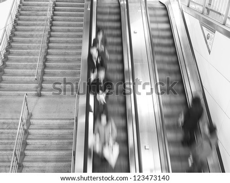 People rush on escalator motion blurred in monochrome background - stock photo