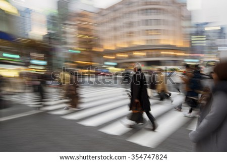 People rushing at heart of the Ginza shopping district in Tokyo. The iconic  Ginza Wako building is at the backround. - stock photo