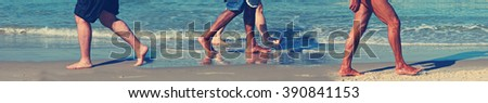 People's bare feet walking along the sea beach with a wave's surf blurry in the background. Toned vintage colors. Panoramic photo