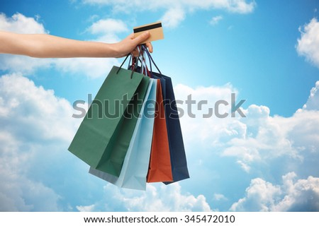 people, sale and consumerism concept - close up of woman with shopping bags and bank or credit card over blue sky and clouds background - stock photo