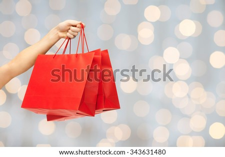 people, sale, consumerism, advertisement and commerce concept - close up of hand holding red blank shopping bags over holidays lights background - stock photo
