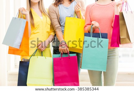 people, sale, consumerism and lifestyle concept - close up of happy teenage girls or young women with shopping bags