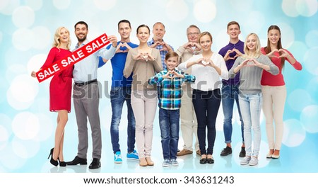 people, sale, discount and shopping concept - happy people with red sign showing heart shape