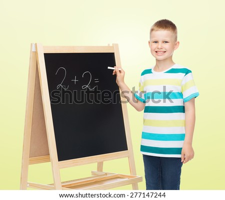 people, school, children, mathematics and education concept - happy little boy with blackboard and chalk writing math exercise over yellow background - stock photo
