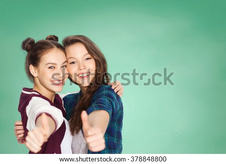 people, school, education, gesture and friends concept - happy smiling pretty teenage student girls hugging and showing thumbs up over green chalk board background - stock photo