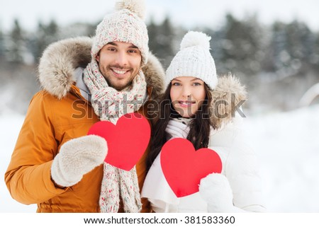 people, season, love and valentines day concept - happy couple holding blank red hearts over winter landscape - stock photo
