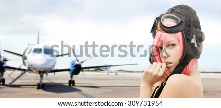 people, sexuality, aviation and role-playing games concept - pink hair girl in aviator helmet over plane in airport background - stock photo