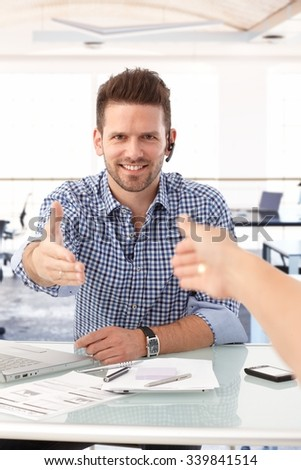 People shaking hand over office desk, casual businessman smiling. - stock photo