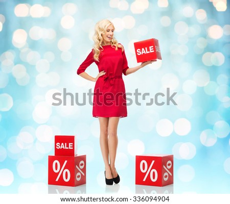 people, shopping, discount and holidays concept - smiling woman in red dress holding cardboard box with sale and percentage sign over blue holidays lights background - stock photo