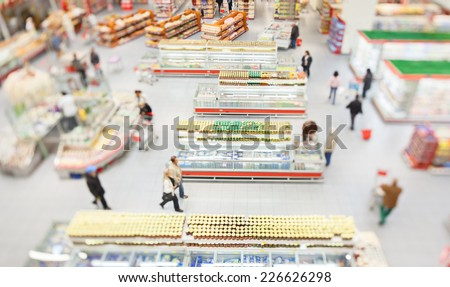 People shopping in a large supermarket shot with a tilt and shift lens with the focus on the racks - stock photo