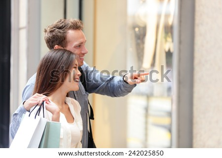 People shopping in Hong Kong Central. Couple looking at shop windows holding shopping bags. Urban mixed race Asian Chinese woman shopper and Caucasian man smiling happy living in city. - stock photo