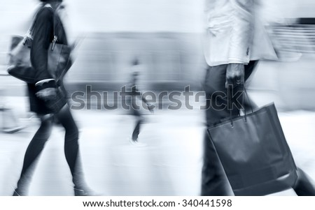 people shopping in the city in motion blur and blue tonality - stock photo
