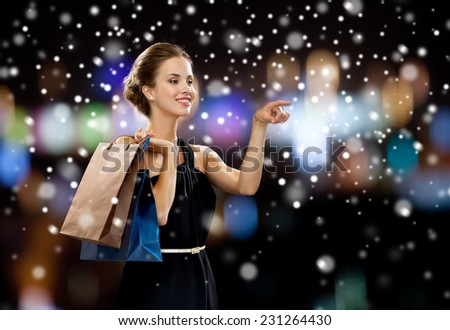 people, shopping, sale, christmas and holidays concept - smiling woman in dress with shopping bags over night lights and snow background - stock photo