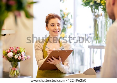 people, shopping, sale, floristry and consumerism concept - happy smiling florist woman with clipboard and man or customer making order at flower shop