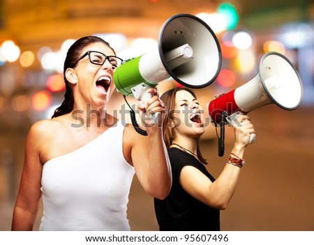 people shouting with megaphone at city by night