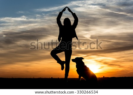 People Silhouette / Girl dances with her dog in the sunset