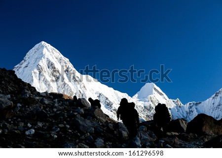 People silhouette hiking in mountains. Hikers in Himalaya Mountains over Pumo ri snow high peak - stock photo