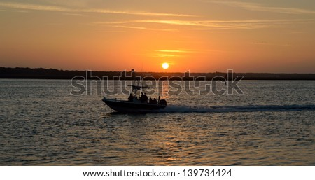 People silhouetted on a boat at sunset Florida, USA.