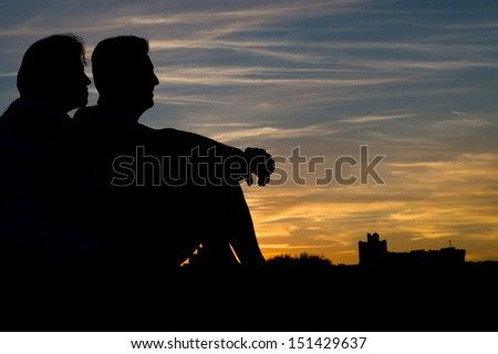 People silhouettes at sunset a clear summer night