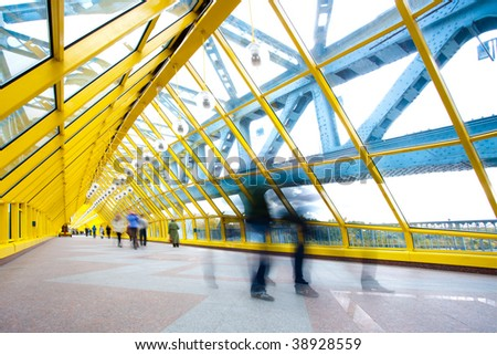 People silhouettes in motion in yellow corridor - stock photo