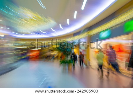 People silhouettes in the shopping mall in motion blur - stock photo