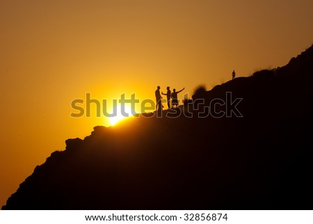 People silhouettes on a mountainside over sunset