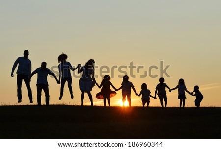 People silhouettes on sunset meadow having fun - stock photo