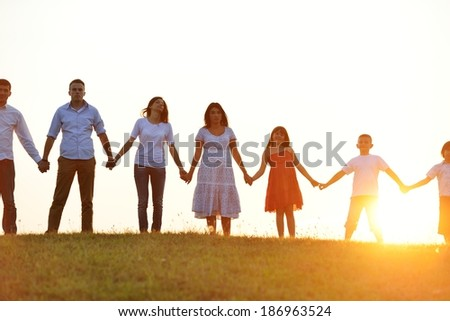 People silhouettes on sunset meadow having fun - stock photo