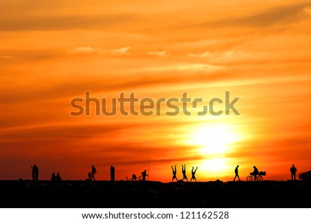 People silhouettes with different expression on the sea sunset embankment