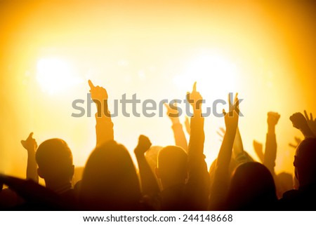 People silhouettes with raised hands enjoying a concert at nightclub - stock photo