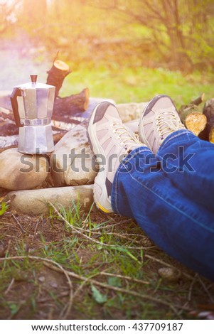 People sitting around a fire at dawn and waiting until the coffee is ready.
