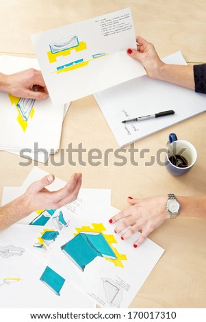 People sitting around a table, going over various product design sketches. - stock photo