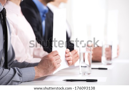 people sitting at auction drinking water. men and women showing cardboards aloft - stock photo