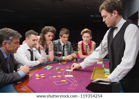 People sitting at table at the casino playing poker - stock photo