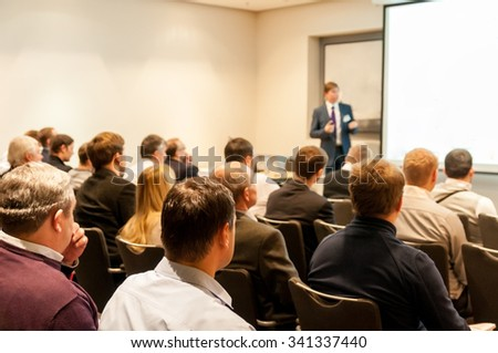 people sitting at the business conference and speaker at the screen - stock photo