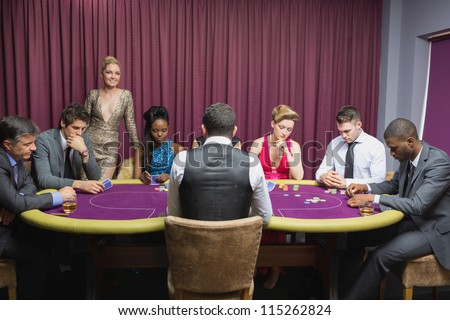 People sitting at the casino table with woman standing and smiling - stock photo