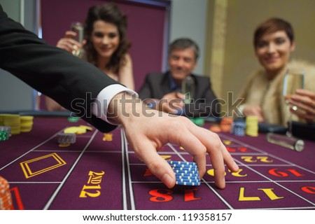 People sitting at the table while placing bets