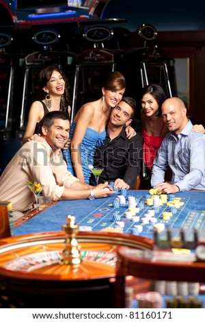 people sitting by the roulette table, posing happy - stock photo
