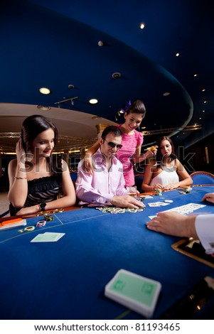 people sitting in a casino, playing poker, man with glasses winning - stock photo
