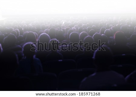 People sitting in an audience facing towards a bright light with flare effect at a live performance or cinema - stock photo