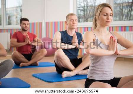 People sitting in lotus position during yoga class - stock photo