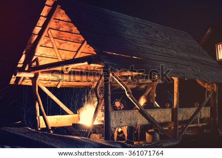 People sitting next to fire at night in the wooden gazebo - stock photo