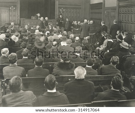 People sitting on benches in courtroom
