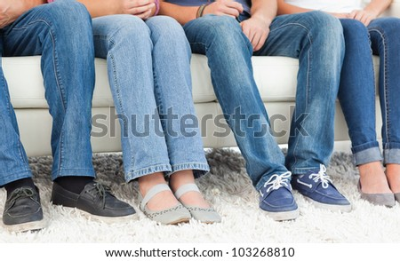 People sitting on the couch with the camera shot on their feet - stock photo