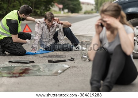 People sitting on the road after car crash - stock photo