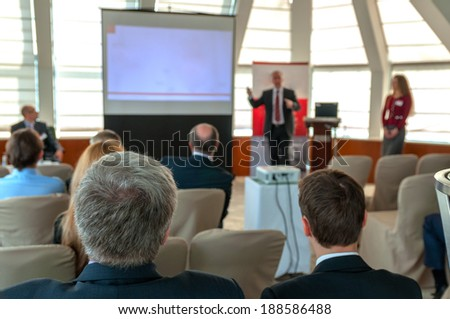 people sitting rear at the business conference and speaker near the screen - stock photo