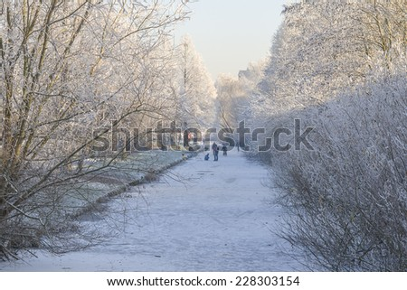 People skating and sleighing on a frozen ditch in the Netherlands - stock photo