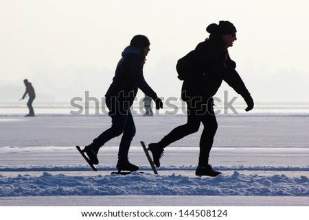 People skating on a frozen lake, Holland - stock photo