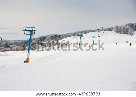People skiing and snowboarding on a slope at ski resort